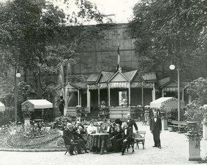Группа посетителей за столом в саду ресторана Контан (крайний слева сидит владелец ресторана Альмир Жуэн).