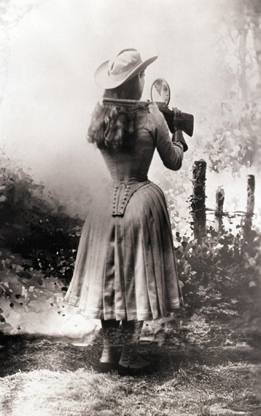 Annie Oakley shooting over her shoulder using a hand mirror - c. 1885-1901.jpg