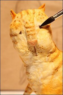 Тоненькой кисточкой белкой расписываем коту лицо.