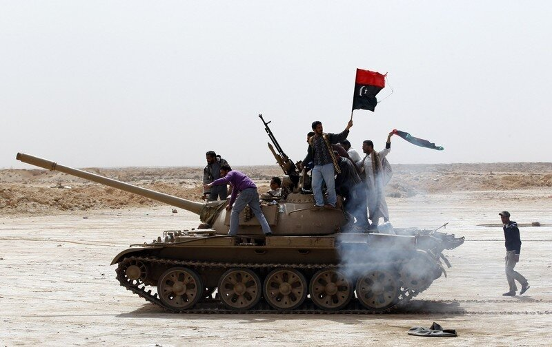 Rebels wave a Kingdom of Libya flag as they ride on top of a tank on the outskirts of Ajdabiyah, on the road leading to Brega
