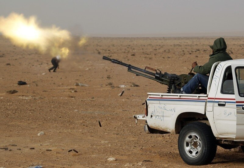 A rebel fighter fires an anti-aircraft gun during a battle near Ras Lanuf