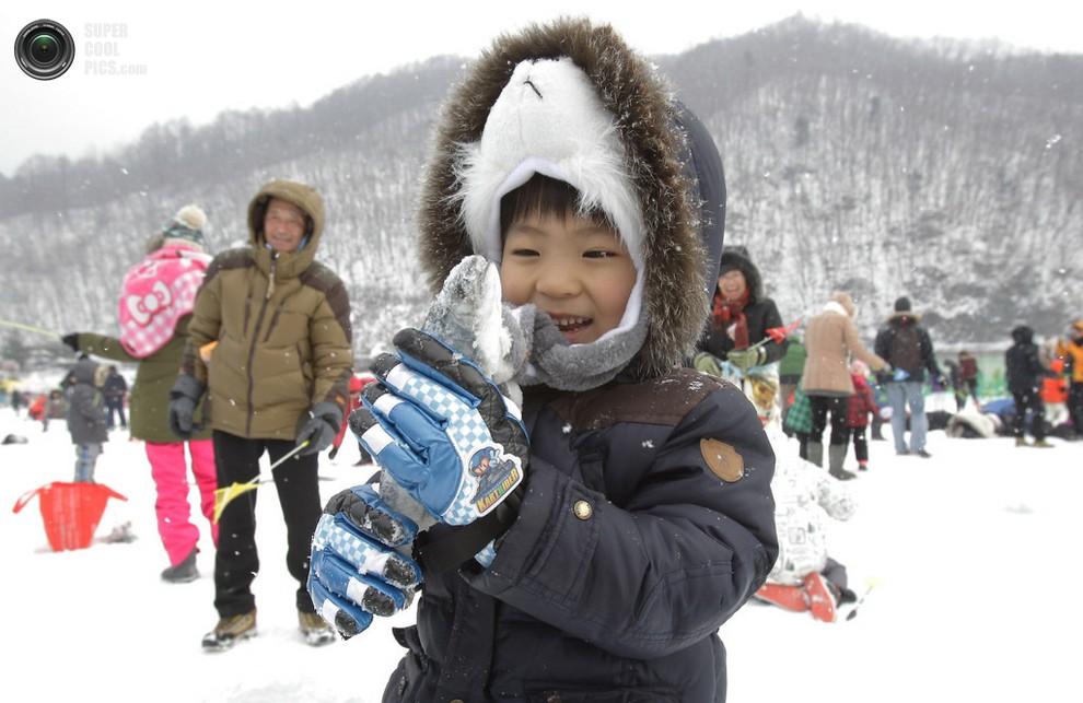 Ребёнок демонстрирует пойманную форель во время Хвачхонского ледяного фестиваля ловли форели, Хв