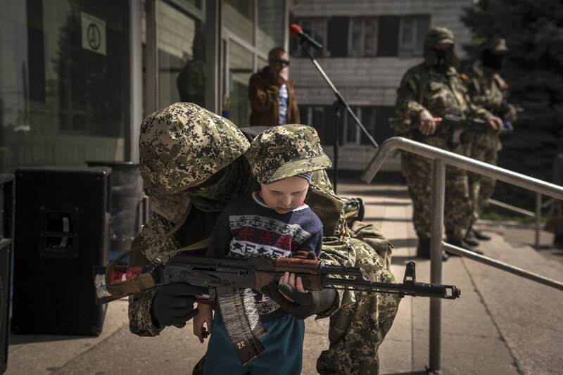 A pro-Russia militia member standing guard outside a seized government building allows a child to partially hold his gun.