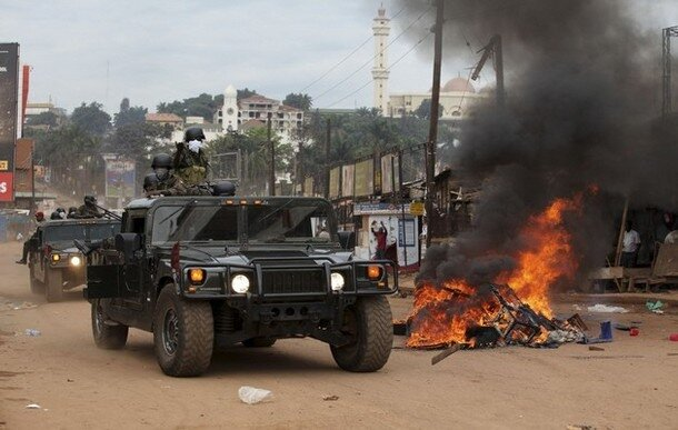 Ugandan military police officers patrol along a barricaded street during demonstrations in Kampala