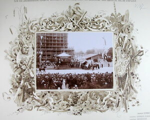 Горожане на [площади] в момент прибытия императора Николая II и императрицы Александры Федоровны у часовни при строящемся православном соборе.