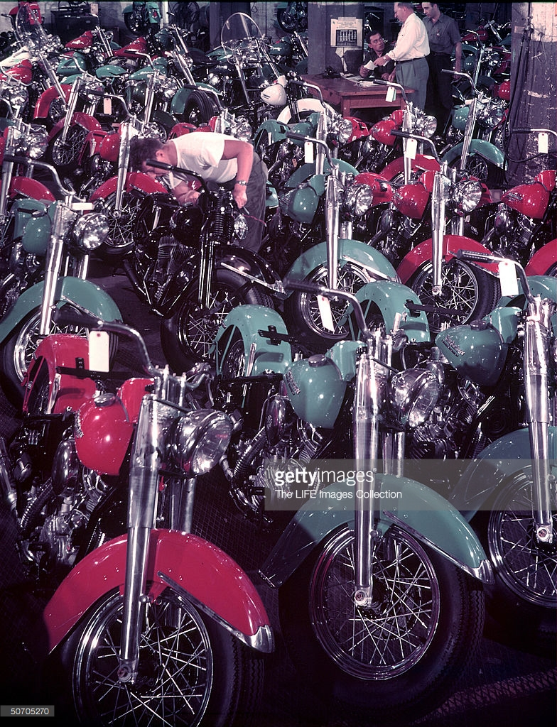 1950 Mechanic checking out Harley Davidson motorcycle in room filled with Harleys by Jerry Cooke.jpg