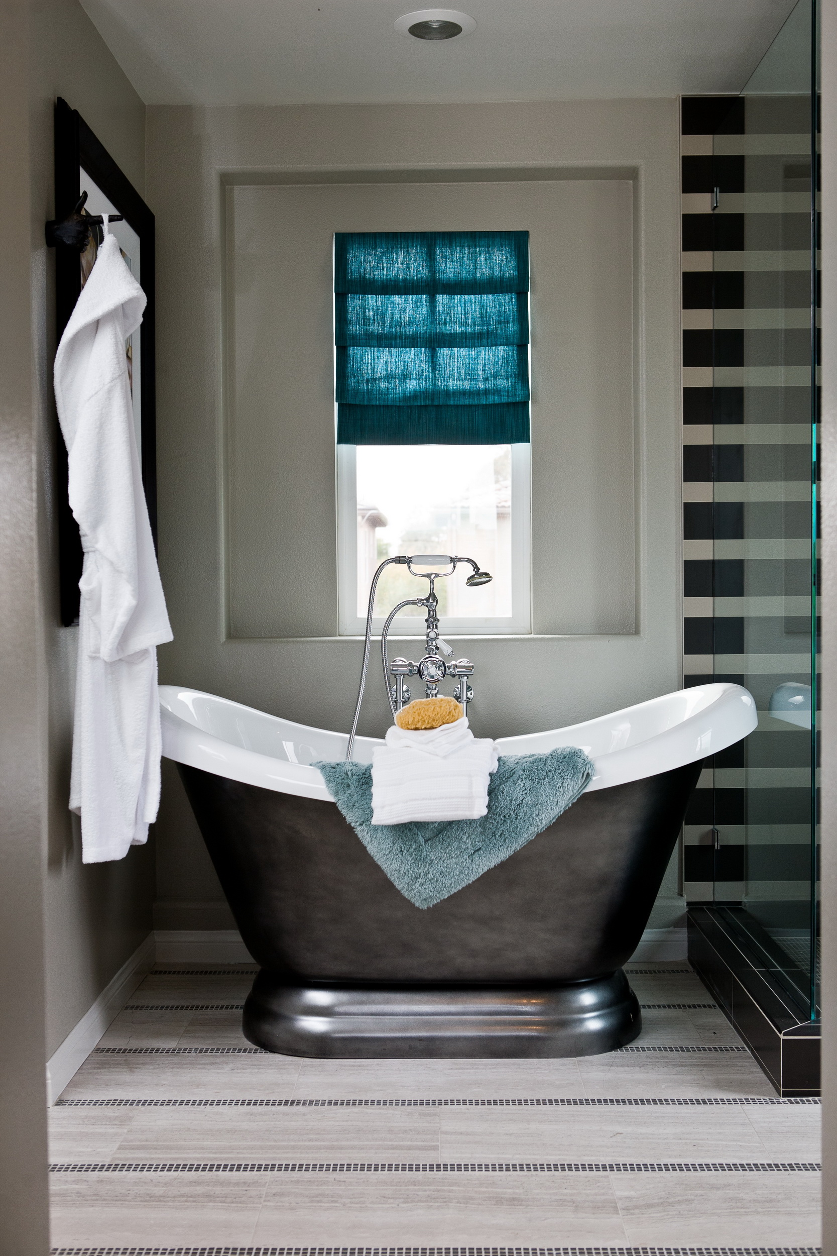 Интерьер ванной комнаты. Ванна из металла. Стеклянная перегородка с черными полосами. Серый, белый, бирюзовый.