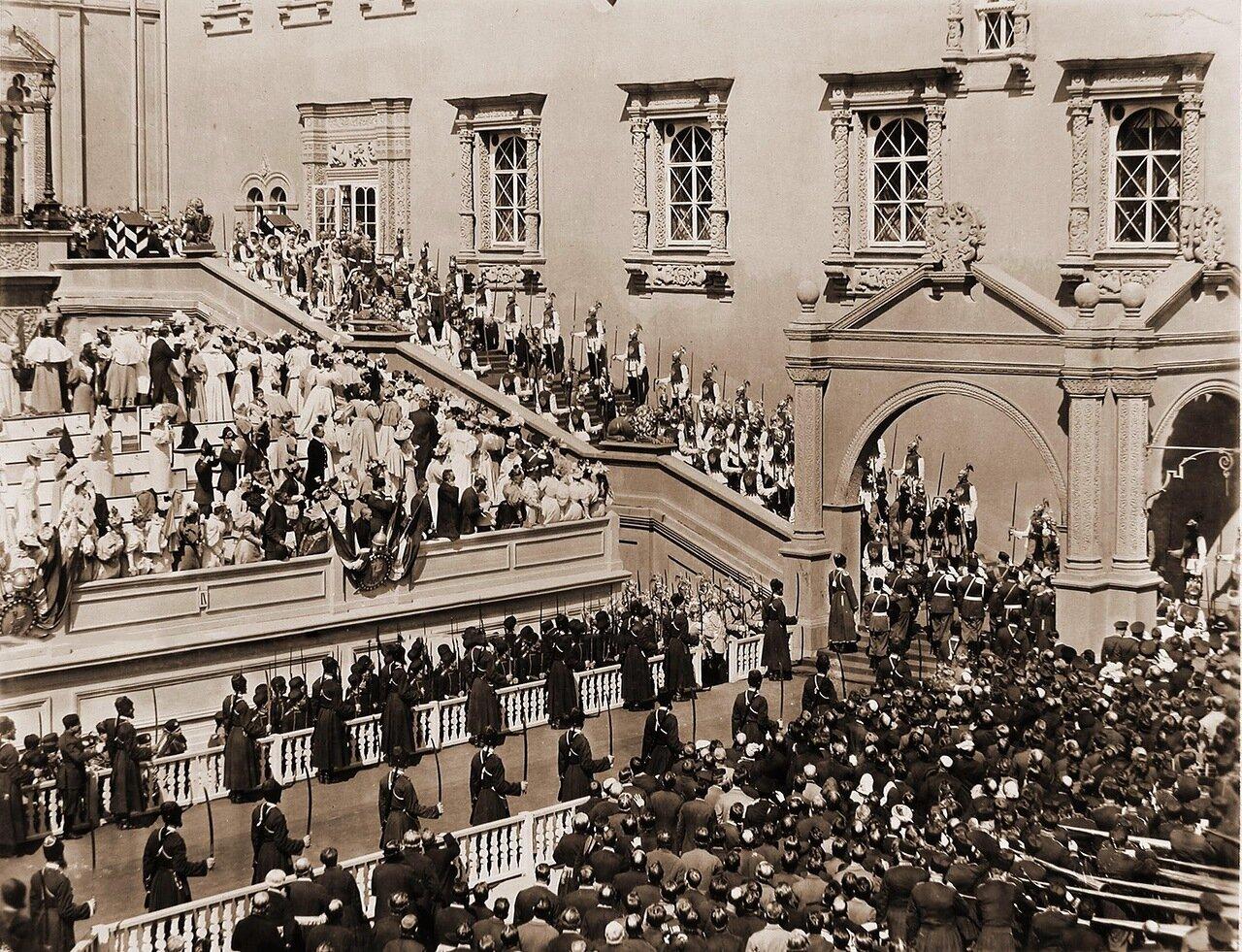 Император Николай II, императрица Александра Федоровна, члены императорской фамилии в сопровождении свиты спускаются по ступеням Красного крыльца Грановитой палаты; за императором (чуть правее) - его августейшие ассистенты: великие князья