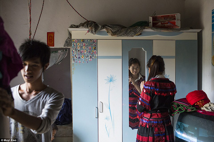 18-летняя Сяо Инь причесывается, пока ее 17-летний муж Сяо Цин готовится к выходу. У пары есть годов