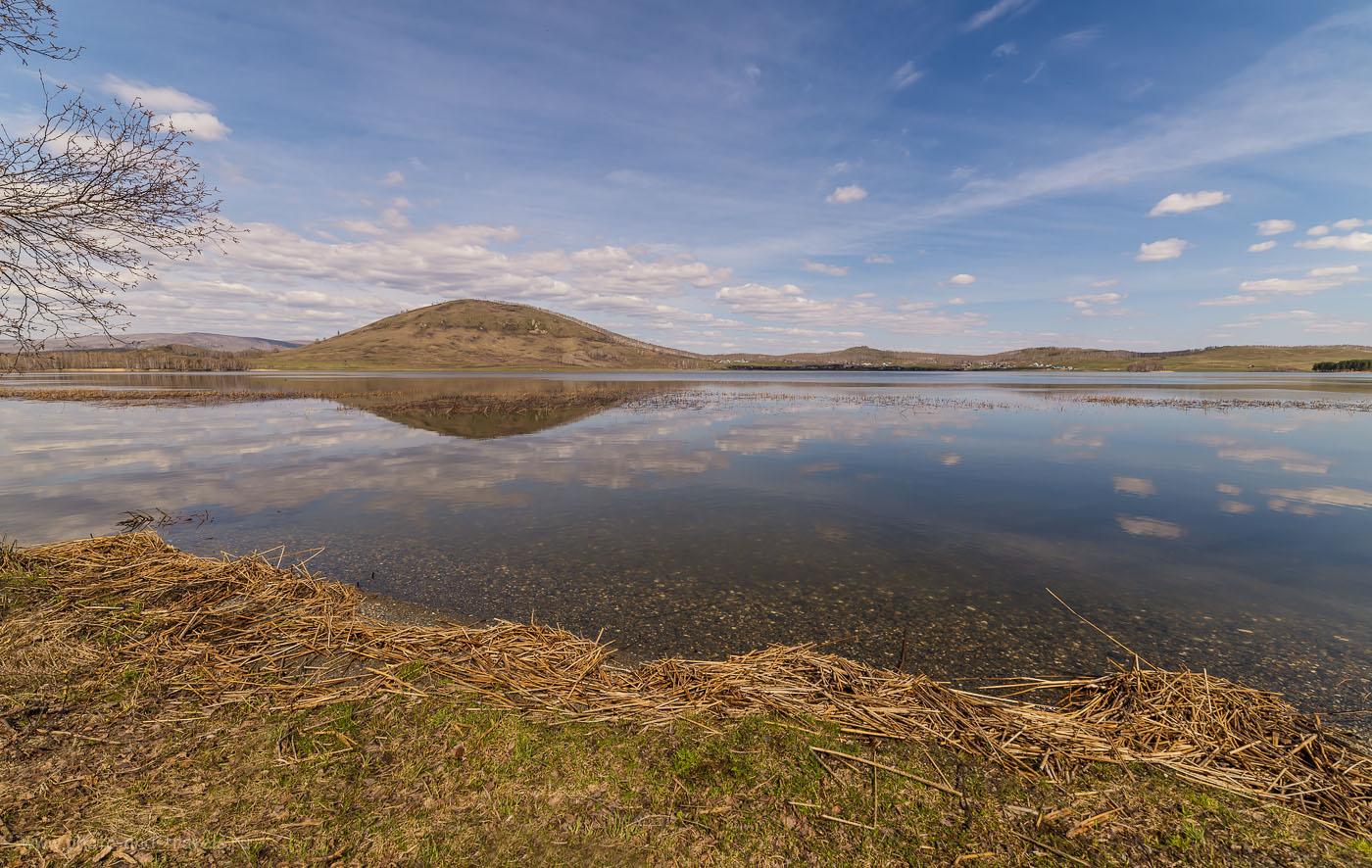 Фотография 2. Озеро Аушкуль и гора Ауштау. На том берегу – деревня Старобайрамгулово. Куда поехать на отдых в Башкирии. На снимке гора кажется небольшим холмиком, поскольку снимал я на суперширокоугольный объектив Samyang 14 mm f/2.8, который «скрадывает» размеры объектов. 1/320, -0.67, 8.0, 100, 14.