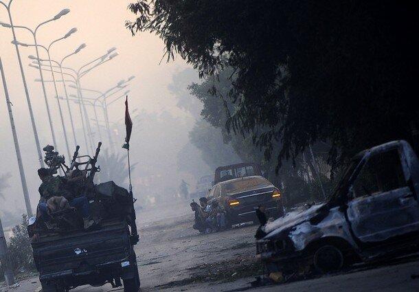 Rebel fighters patrol the streets in a n