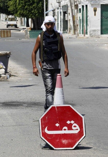 A rebel fighter stands at a checkpoint in a street in Tripoli