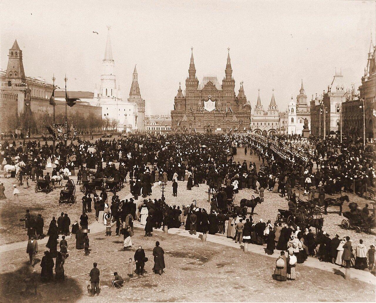 Жители Москвы и окрестностей на Красной площади в дни объявления даты священного коронования;справа, перед торговыми рядами - дивизионы кавалергардского и лейб-гвардии конного полков