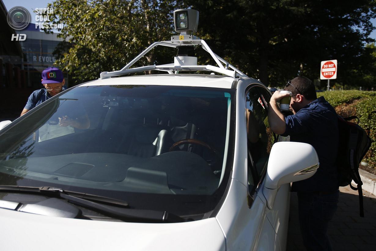 США. Маунтин-Вью, Калифорния. 13 мая. Журналисты разглядывают салон беспилотного автомобиля Google.