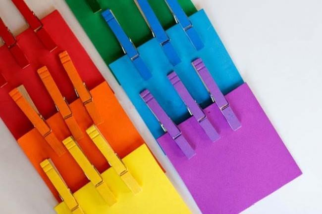 1. Возьмите цветной картон и вырежьте квадратики (8?8 см). Также купите деревянные прищепки и покрас