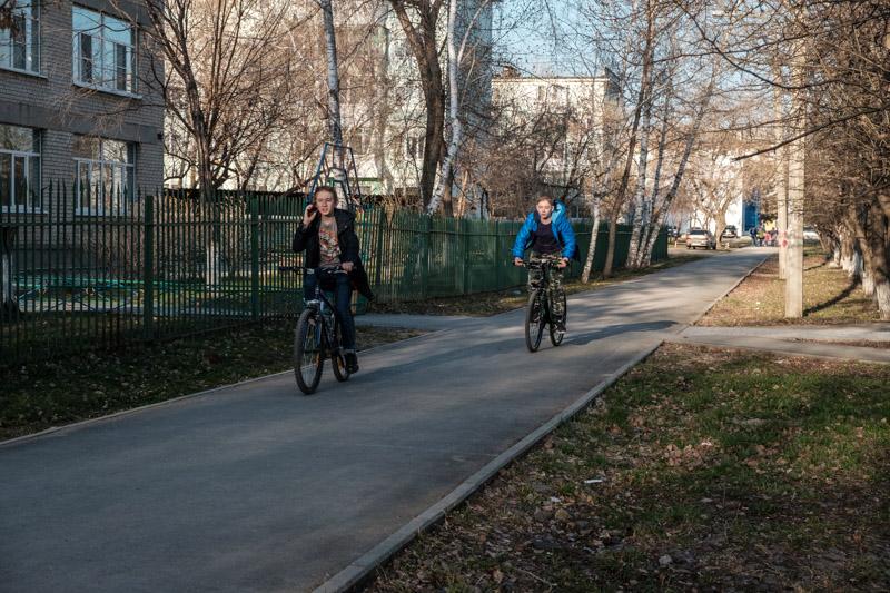 ребята едут на велосипедах и разговаривают на телефонах