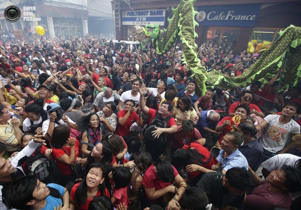Люди ловят деньги и другие подарки, которые бросают китайские бизнесмены во время празднования Н