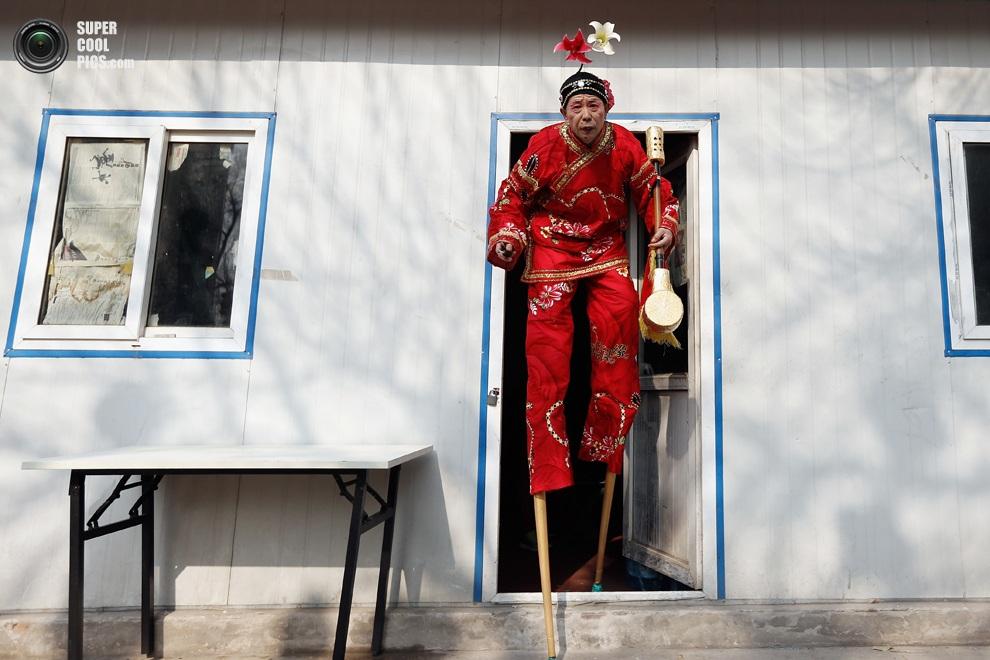 Пекинский актёр на ходулях направляется в парк на церемонию открытия Праздника весны.(Lintao Zh