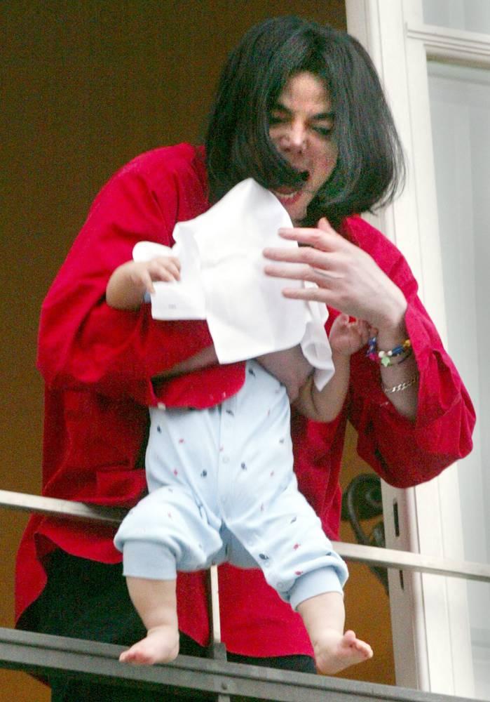 Джексон держит своего сына Принца Майкла II, накрытого полотенцем, стоя на балконе берлинской гостин