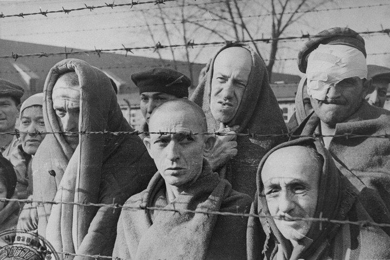 Бывшие узники концлагеря Освенцим у забора из колючей проволоки после освобождения