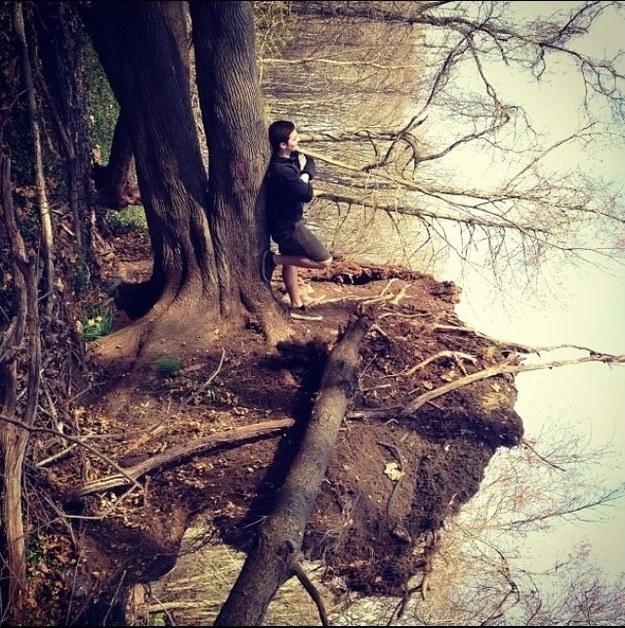 Парень вовсе не стоит у дерева, а лежит.