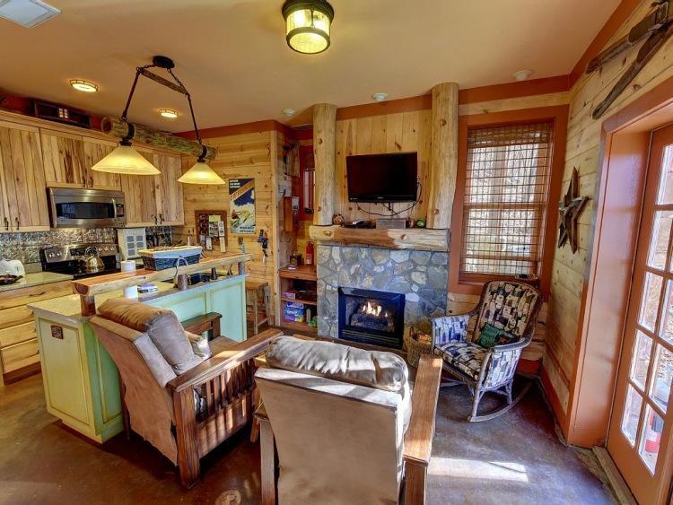 4. На первом этаже находится уютный зал с камином, а также кухонный угол с островком и барными стуль