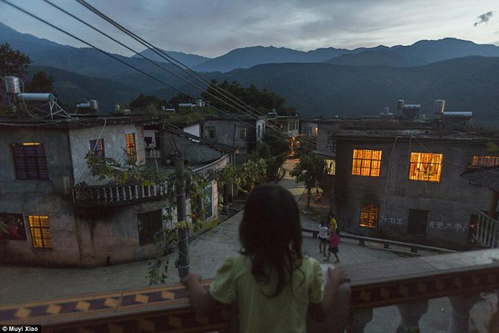 7-летняя Сяо Юань смотрит на деревню Янси в провинции Юньнань с балкона соседского дома. Ее мама род