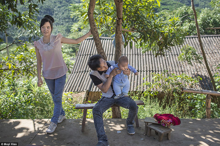 16-летняя Сяо Жун с мужем Сяо Юном и 10-месячным ребенком. Округ Менгла, провинция Юньнань.