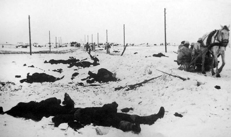 Немецкие солдаты едут на санях мимо убитых красноармейцев.jpg