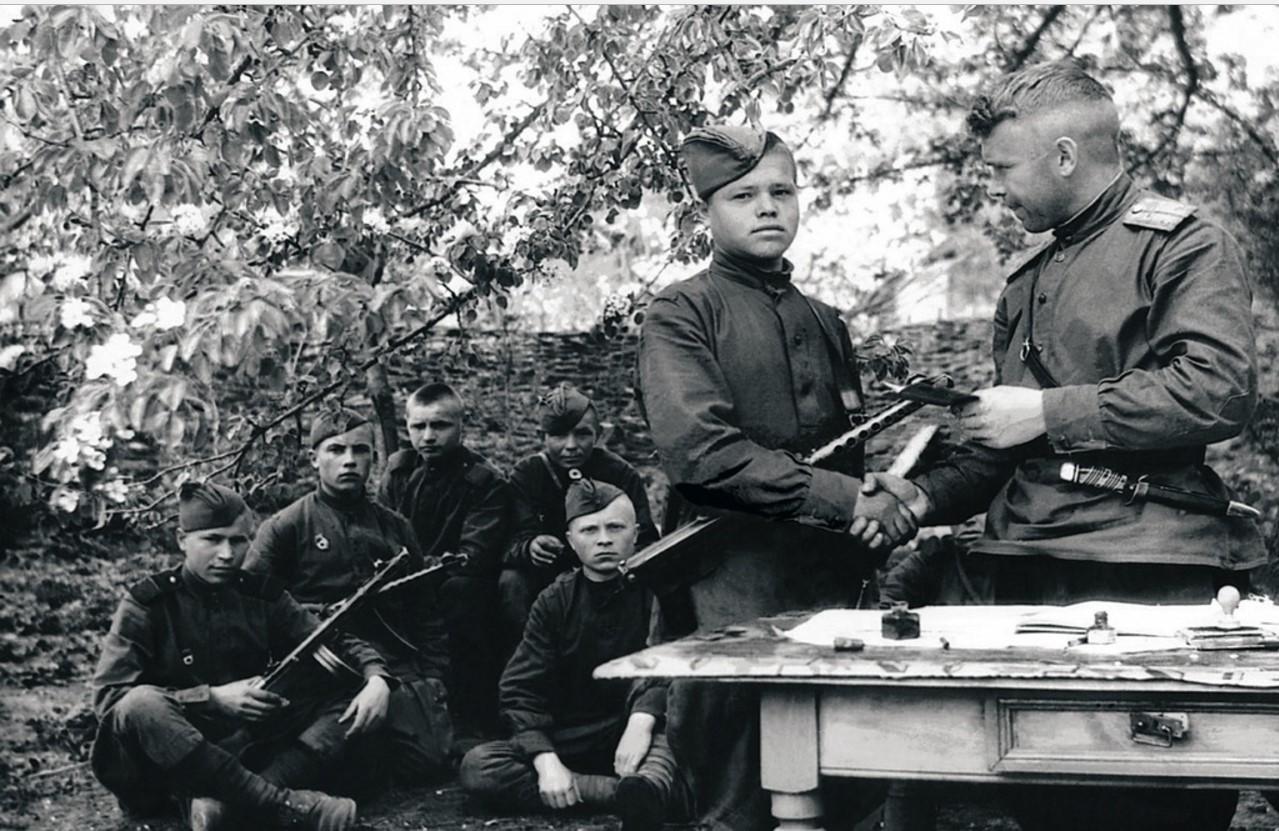 Вручение комсомольских билетов молодым бойцам, отличившимся в боях, помощником начальника политотдела бригады по комсомолу старшим лейтенантом Чередниченко