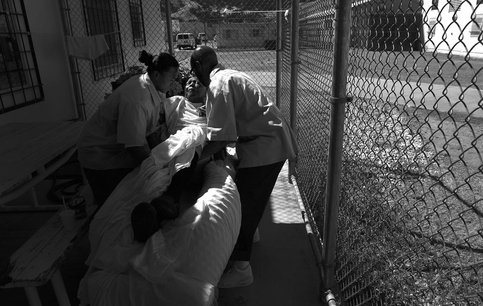 9. Шон Рис (справа) и Джон Пол Мадрона (слева) поднимают заключенного Ричарда Карри с койки во внутр