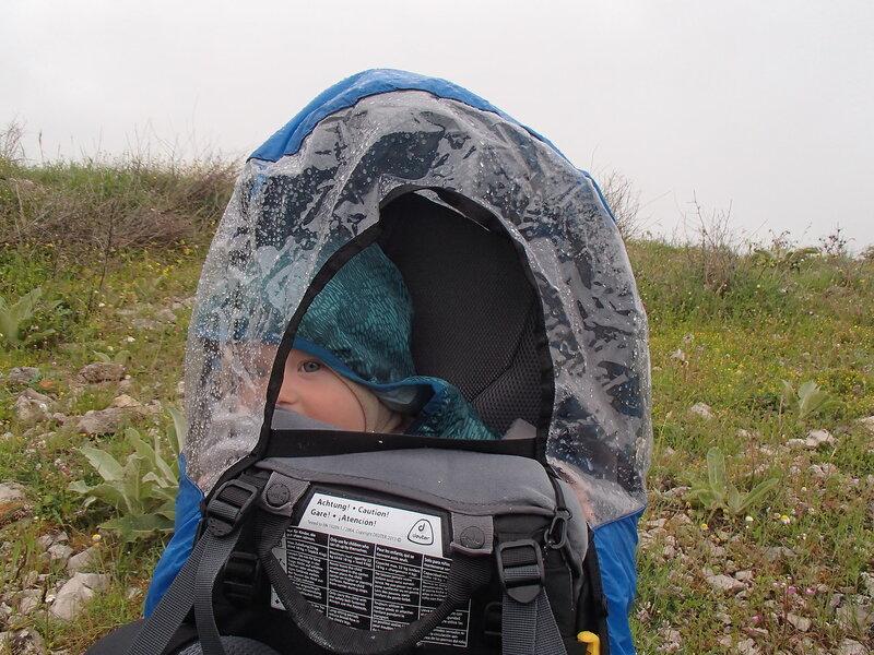 Ребенок (1 год) в пешем походе в рюкзаке Deuter Kid Comfort III с чехлом под дождем