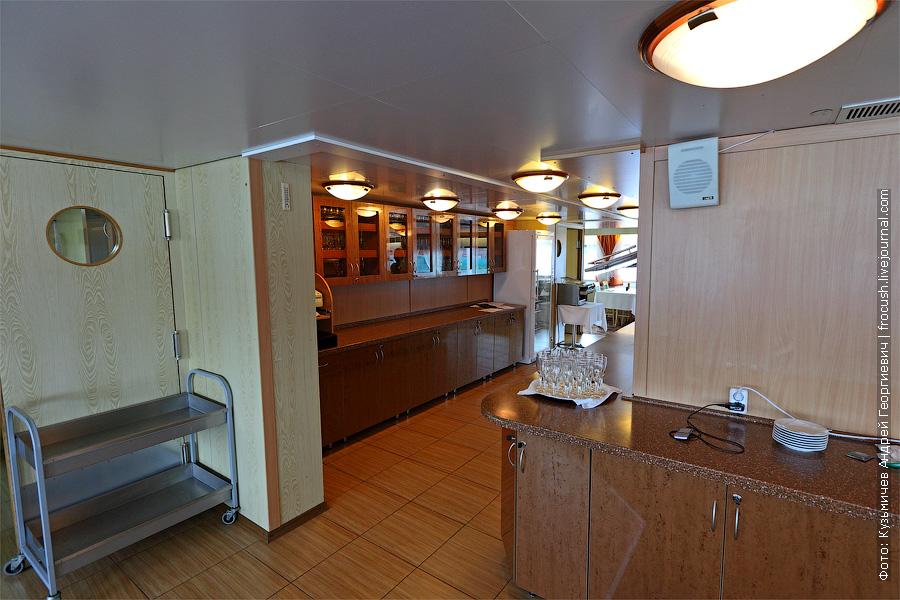 Слева на фото дверь, из которой выходят официанты и разносят блюда по столам. Справа на фото место, где стоит еда во время завтрака – шведского стола. теплоход «Кронштадт»