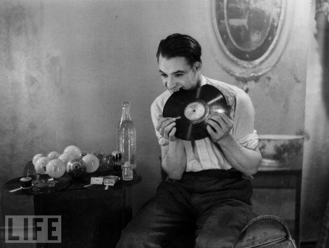 Человек жует  граммофонные пластинки. Рядом с ним стоит стол с лампочками,которые тоже будут сьедены