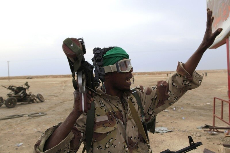 A Libyan government soldier holds a weapon at the west gate of town Ajdabiyah
