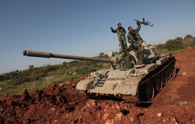 Libyan rebels rise thier weapons ontop o