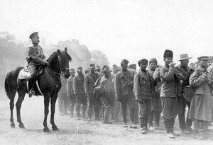 Колонна пленных австрийцев в сопровождении конного конвоира на улице города