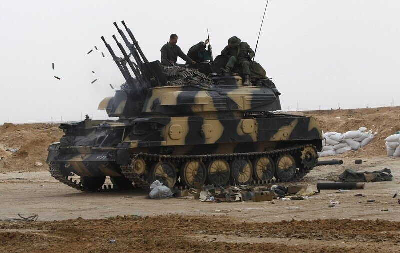 Libyan government soldiers sit on a tank at the west gate of  town Ajdabiyah