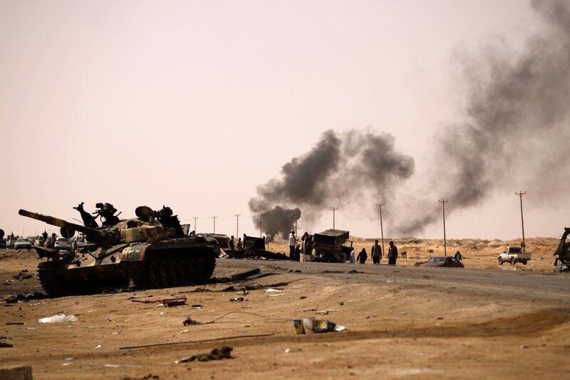 Libyan rebels gather at a site bombed by