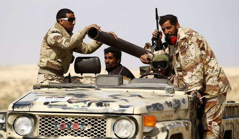 Rebel fighters ride an open pick-up truck mounted with a recoilless rifle as they retreat from the frontline on the road to the east of Brega, in Libya