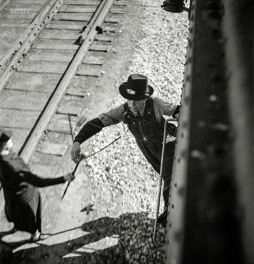March 1943. Dalies, New Mexico. Conductor C.W. Tevis picking up a message from a woman operator on the Atchison, Topeka & Santa Fe between Belen and Gallup