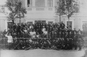 Группа солдат с офицерами у казарм.