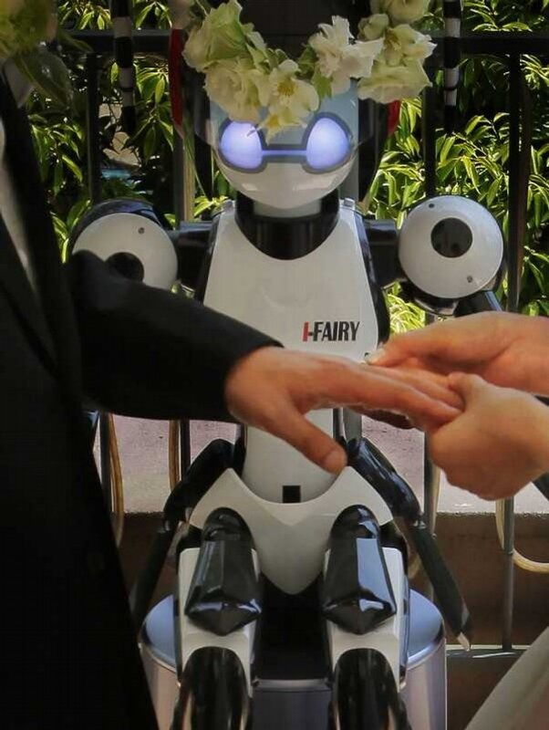 I-Fairy, a four-foot tall seated robot with flashing eyes and plastic pigtails, wearing a wreath of flowers, directs a wedding ceremony. (2010)