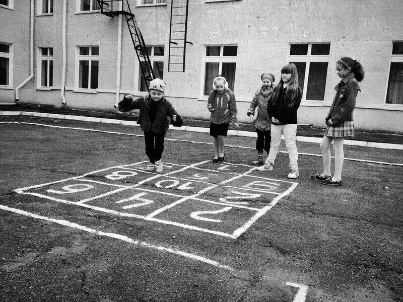 Девчонки играют в прыгалки на школьном дворе