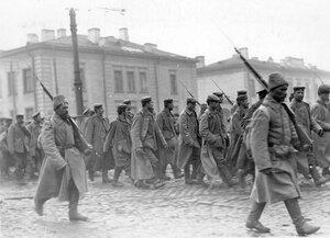Военнопленные под конвоем проходят по одной из улиц города