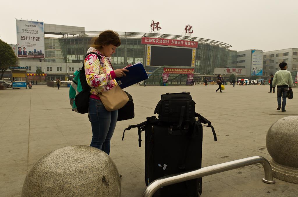 """2. На площади у железнодорожного вокзала в городе Хуайхуа (Huaihua, 怀化). Катя выискивает в нашей волшебной папке название следующей станции на китайском. Нужно как-то доехать до Сянзянсян (Sanjiangxian, 三江县). На фото: """"походный чемодан"""", обычный рюкзак и фоторюкзак Ainogirl. Отзыв о поездке по Китаю на поезде."""