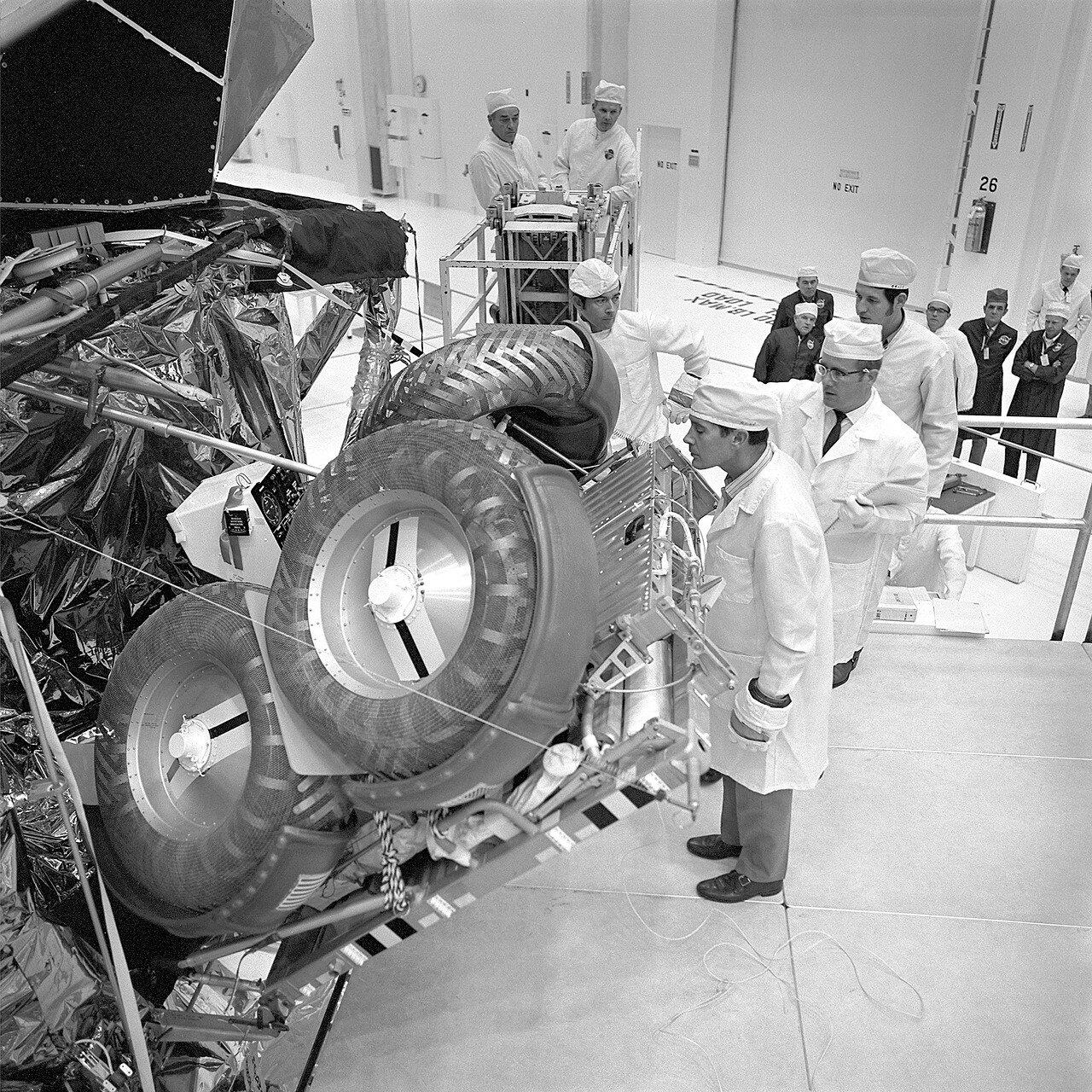 В процессе подготовки космического корабля к старту  возникла необходимость замены отдельных систем и узлов.Было решено заменить все парашюты из-за того, что в августе при посадке «Аполлона-15» один из них не раскрылся. На снимке: Проверка Лунного Ровера