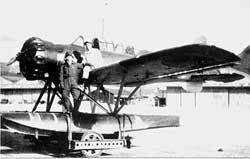 """Nobuo Fujita standing by his Yokosuka E14Y """"Glen"""" seaplane."""