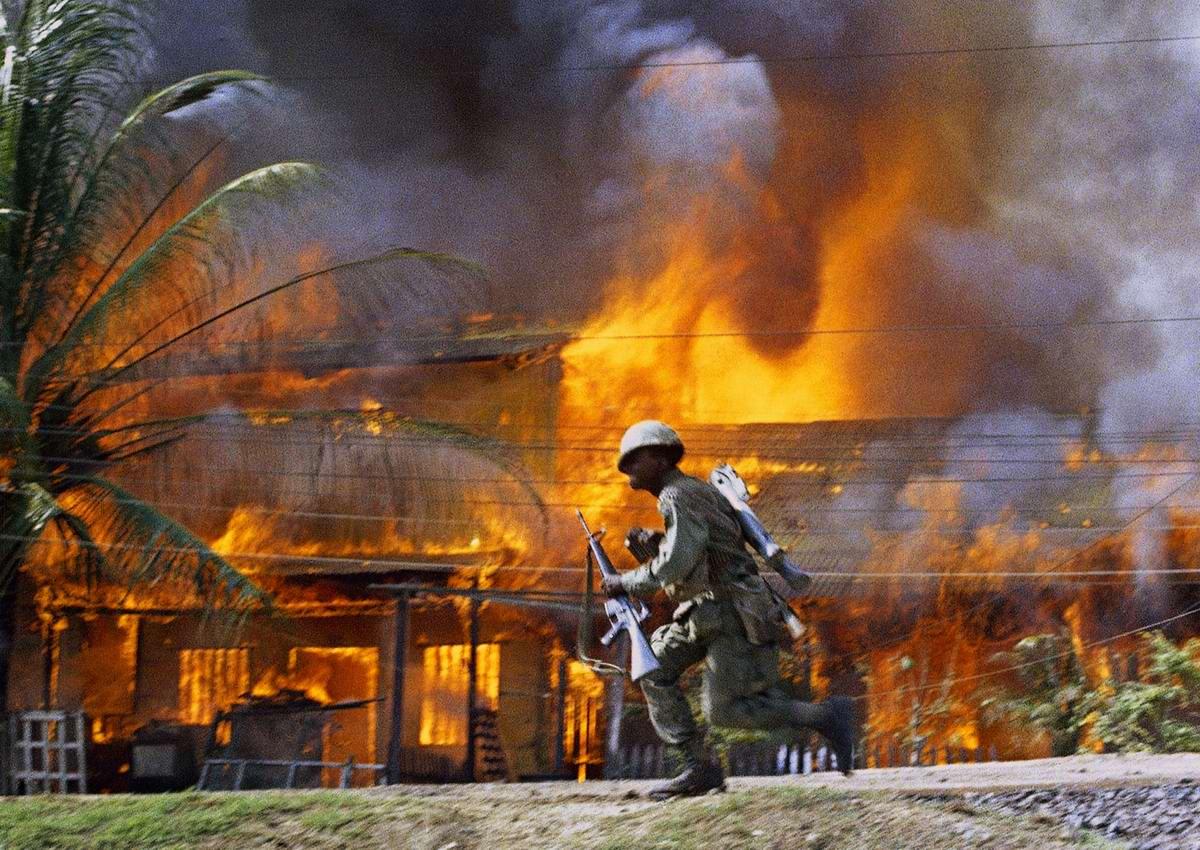 Американский десантник пробегает мимо горящего здания в Сайгоне (июнь 1968 года)