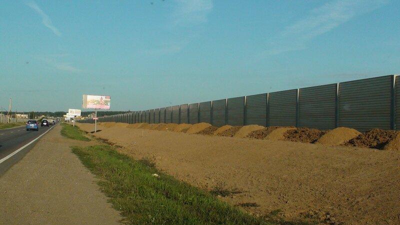 Ровняют насыпь возле поселкового забор